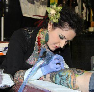 A tattoo artist at her work.